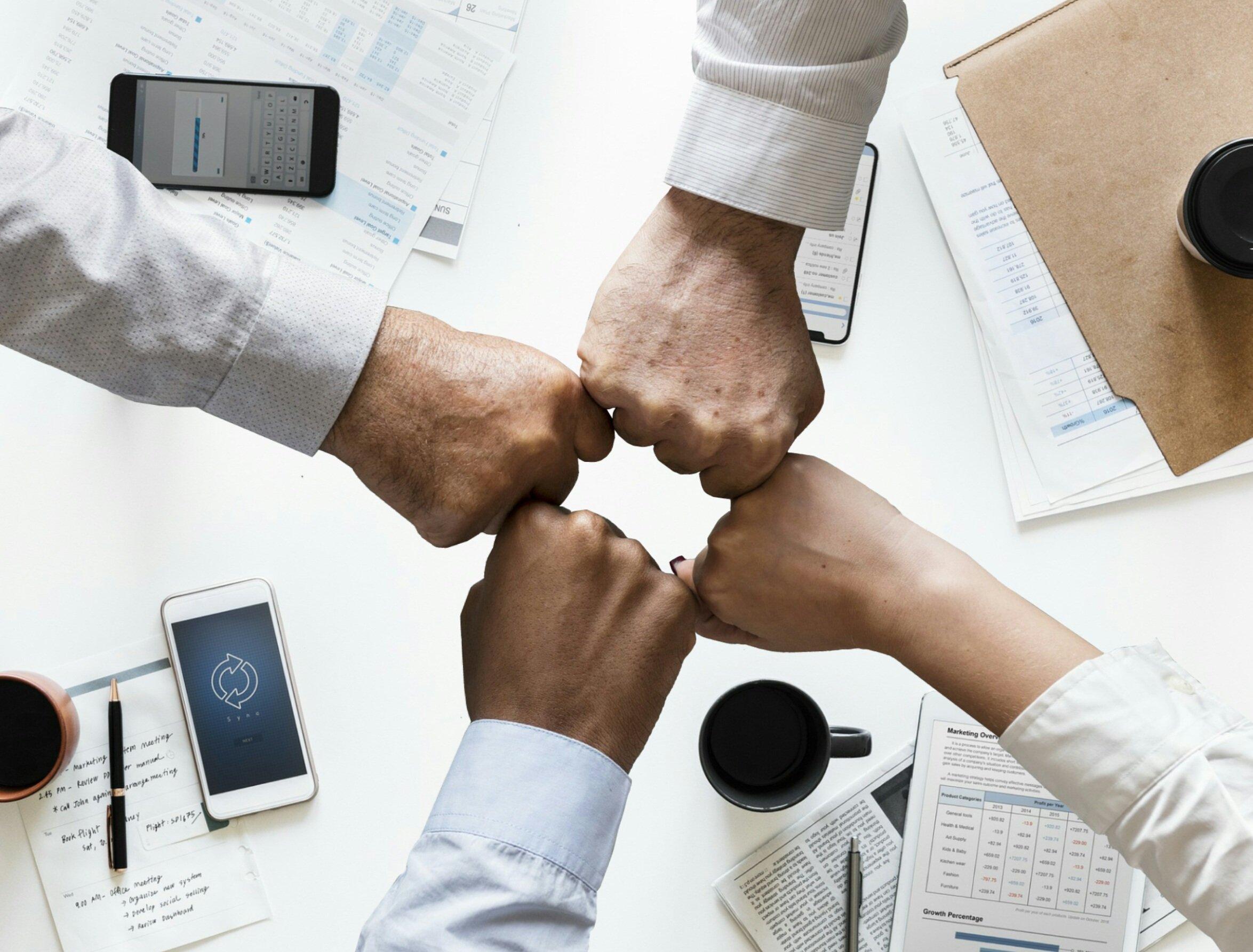 Quatro mãos fechadas em punho se encontram sobre uma mesa com celulares, canecas de café e material de escritório. Fonte: Pixabay License.