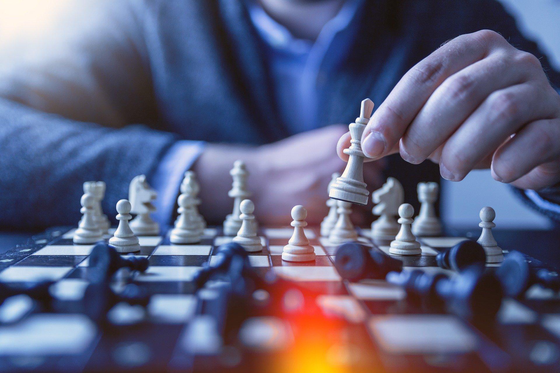 Homem branco movendo uma peça de xadrez no tabuleiro.